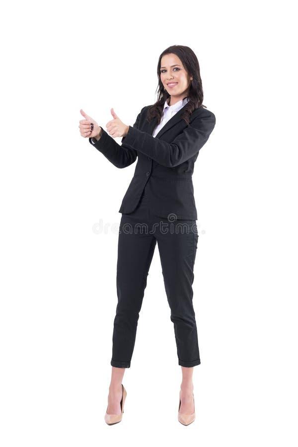 Mulher de negócio bonita elegante de sorriso feliz que mostra os polegares acima com ambas as mãos e que olha a câmera imagem de stock