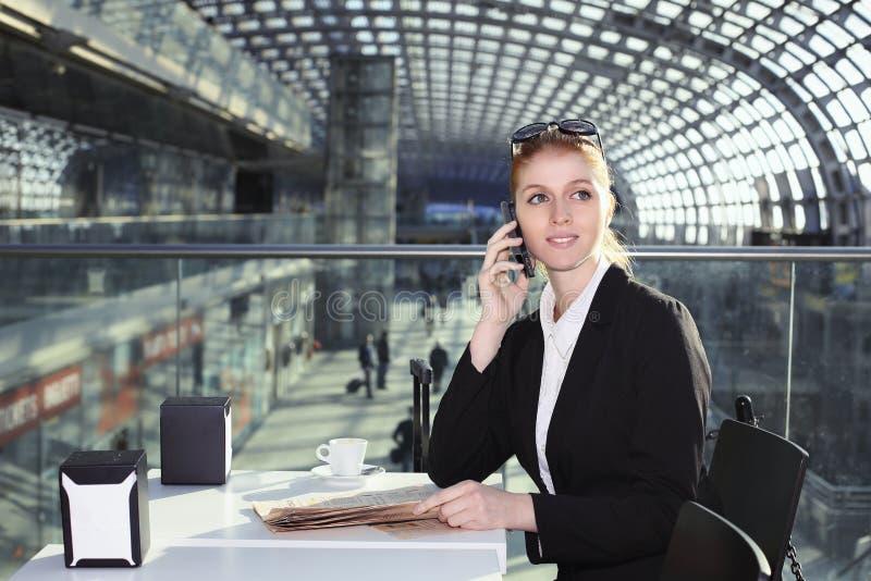 Mulher de negócio bonita no salão de estação de caminhos-de-ferro fotografia de stock
