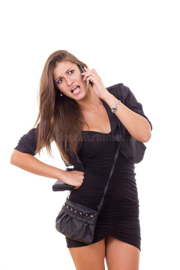 Mulher de negócio bonita nova que tem a discussão sobre o telefone fotografia de stock