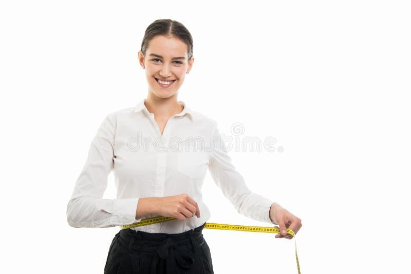 Mulher de negócio bonita nova que usa a fita de medição amarela foto de stock
