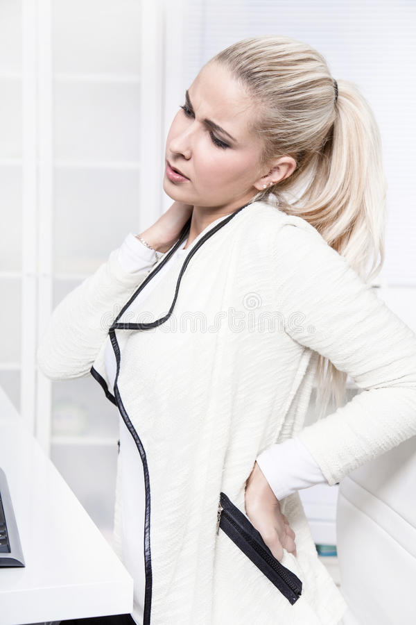 A mulher de negócio bonita nova tem dores nela para trás imagens de stock royalty free