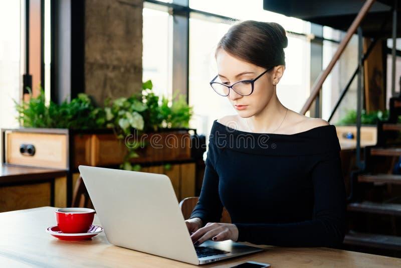 A mulher de negócio bonita nova trabalha em um portátil, usos um smartphone, um freelancer, um computador, analista financeiro, u fotos de stock