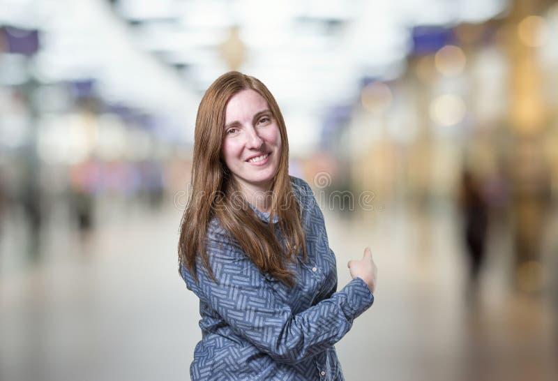 Mulher de negócio bonita que apresenta algo sobre o fundo do borrão imagens de stock royalty free
