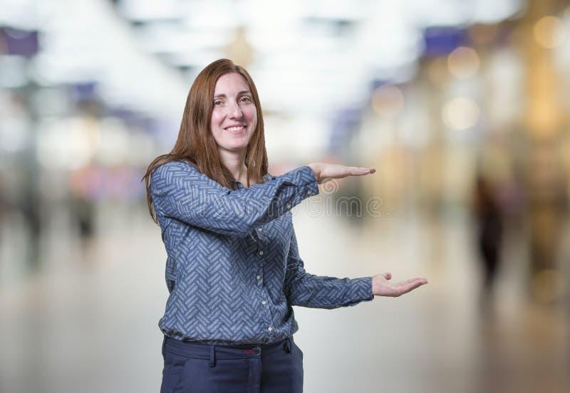Mulher de negócio bonita que apresenta algo sobre o fundo do borrão foto de stock royalty free