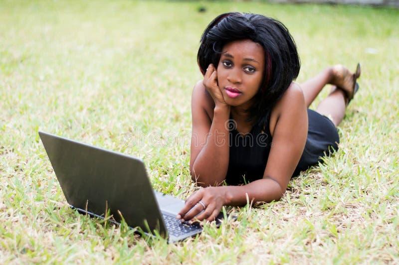 Mulher de negócio bonita que coloca na grama e que usa o portátil imagens de stock royalty free