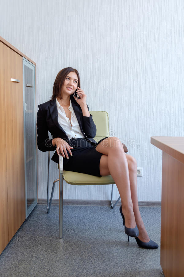 Mulher de negócio bonita que fala no telefone celular e que sorri, na cadeira no escritório imagem de stock royalty free
