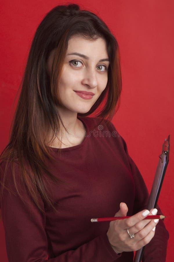 Mulher de negócio bonita que guarda o dobrador do original no fundo vermelho imagem de stock
