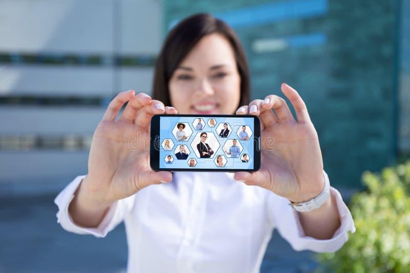 Mulher de negócio bonita que mostra o smartphone com rede social fotografia de stock royalty free