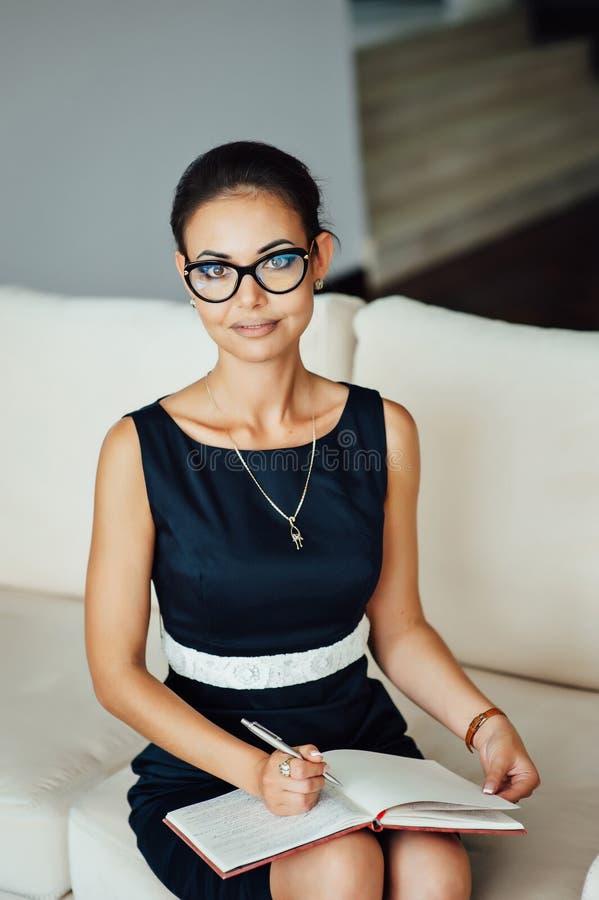 Mulher de negócio bonita que senta-se em um sofá bege em seu escritório imagem de stock