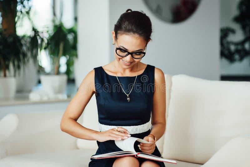 Mulher de negócio bonita que senta-se em um sofá bege em seu escritório fotografia de stock royalty free