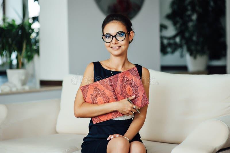 Mulher de negócio bonita que senta-se em um sofá bege em seu escritório fotos de stock royalty free