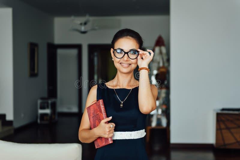 Mulher de negócio bonita que senta-se em um sofá bege em seu escritório foto de stock