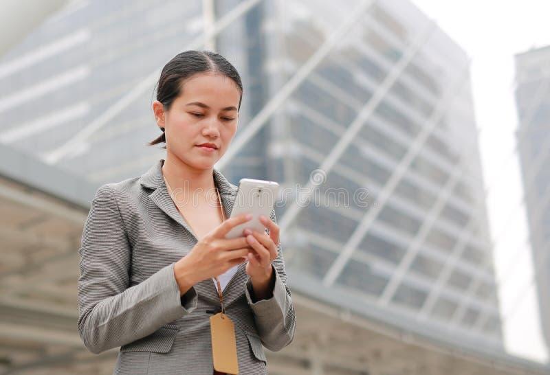 Mulher de negócio bonita que trabalha em um smartphone em suas mãos fora foto de stock