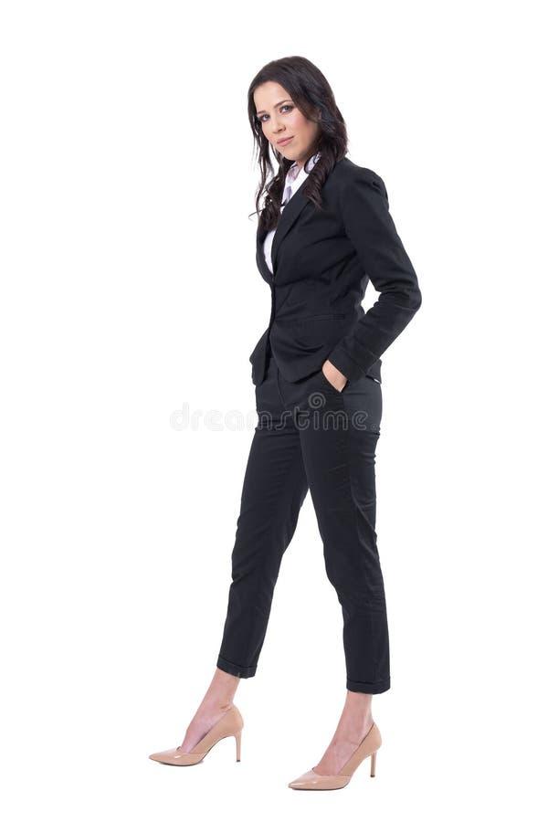 Mulher de negócio bonita segura bem sucedida no terno preto clássico com mãos em uns bolsos que olham a câmera foto de stock