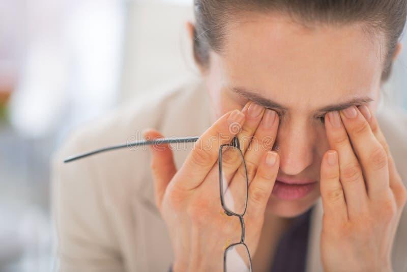 Mulher de negócio cansado com os monóculos no escritório imagem de stock