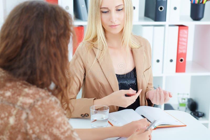 Mulher de negócio caucasiano nova que escuta suas explicações do colega imagens de stock royalty free