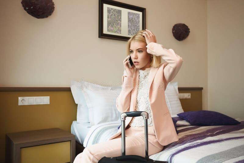 Mulher de negócio chocada que senta-se na sala de hotel foto de stock