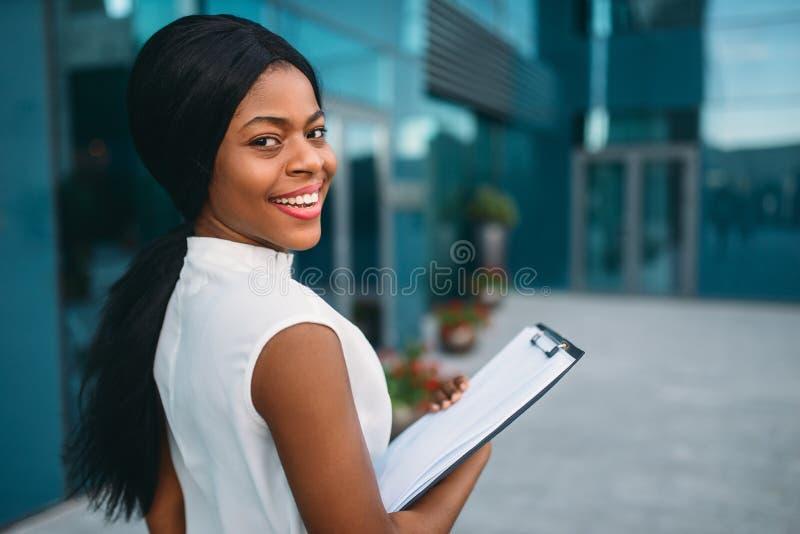 Mulher de negócio com bloco de notas fora, vista traseira fotografia de stock royalty free