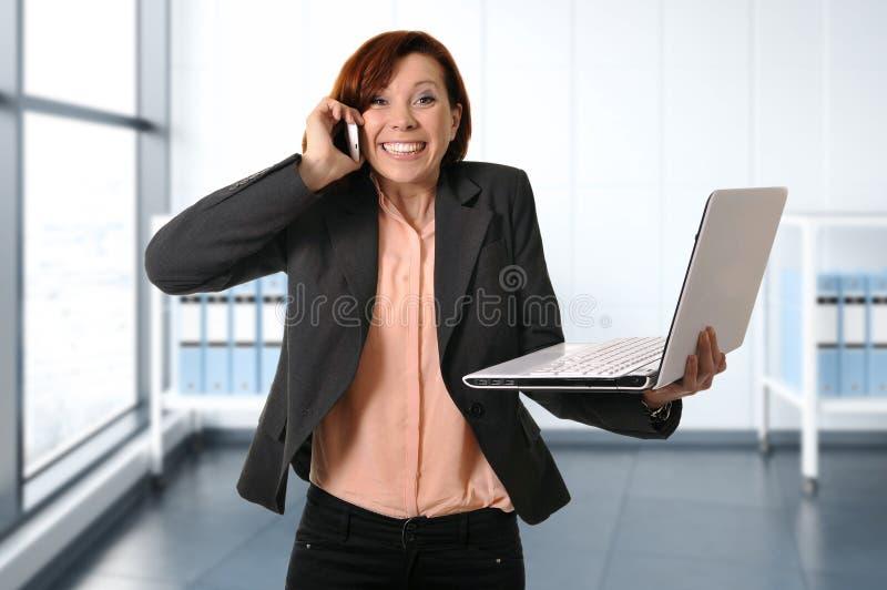 Mulher de negócio com cabelo vermelho no trabalho que sorri com a fala do laptop ocupada no telefone celular foto de stock