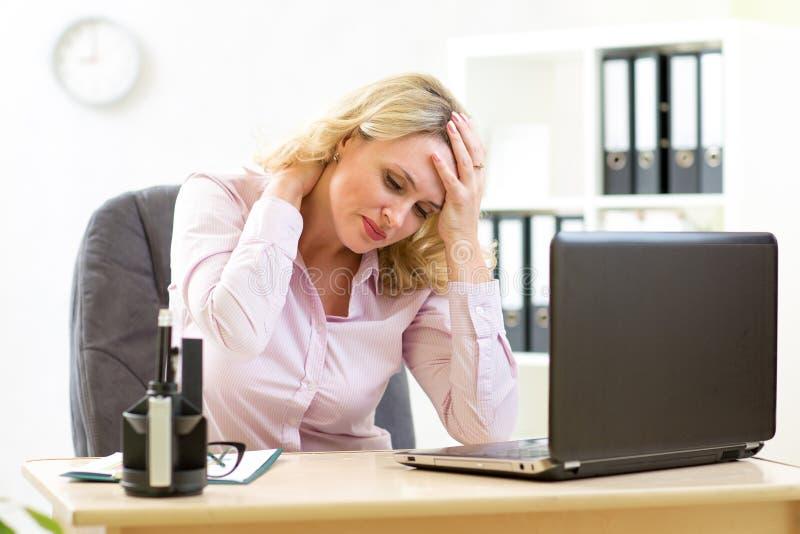 Mulher de negócio com a dor de cabeça que tem o esforço no escritório
