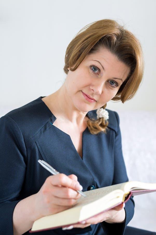 Mulher de negócio com livro e pena à disposição fotografia de stock