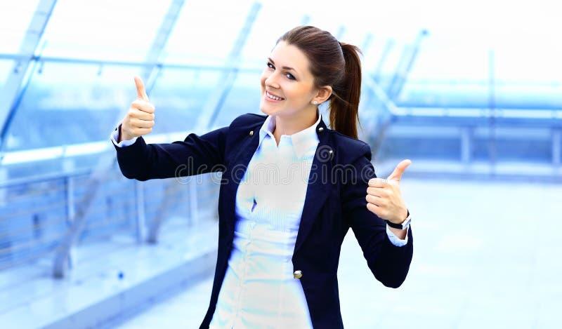 Mulher de negócio com os polegares que olham acima felizes fotografia de stock royalty free