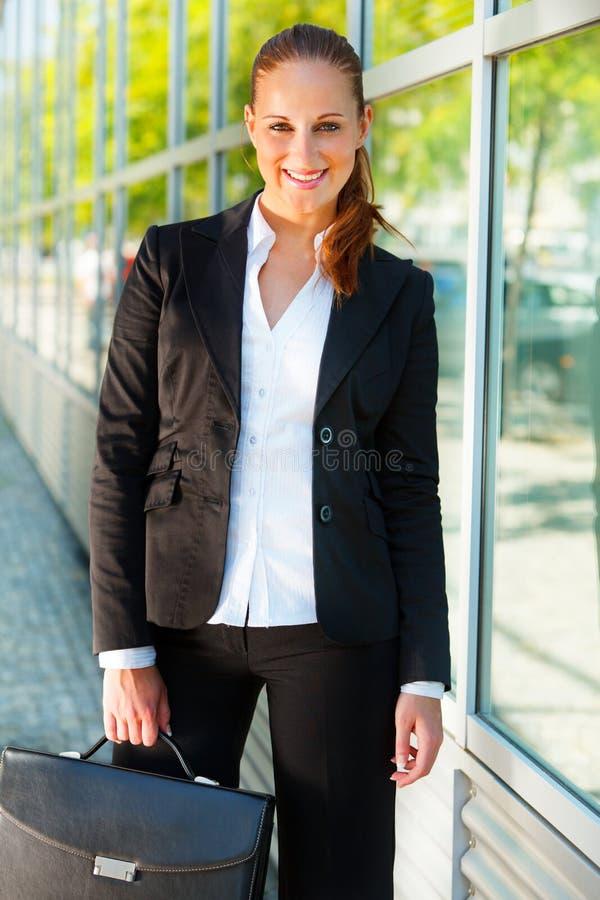 Mulher de negócio com a pasta no prédio de escritórios fotografia de stock