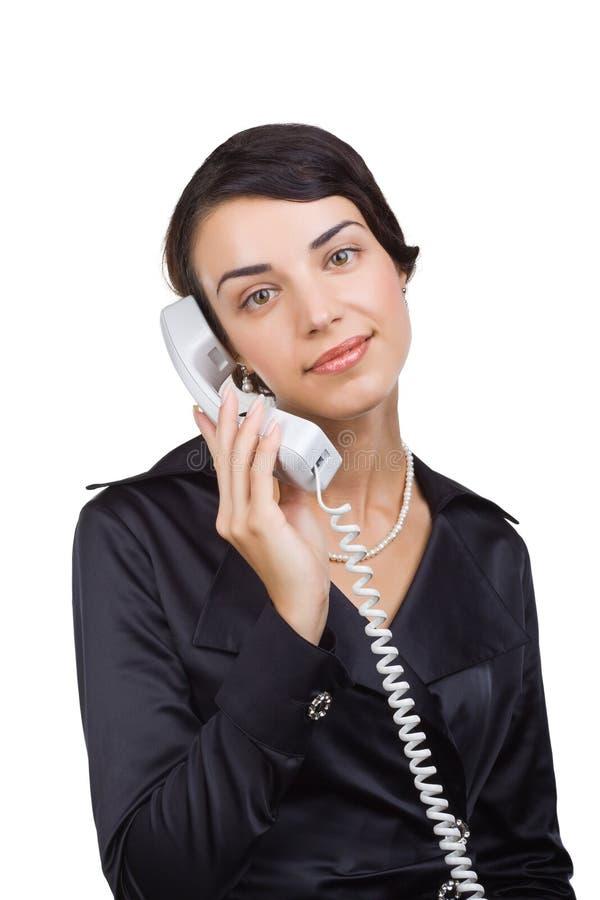 Mulher de negócio com um receptor de telefone à disposicão fotografia de stock royalty free