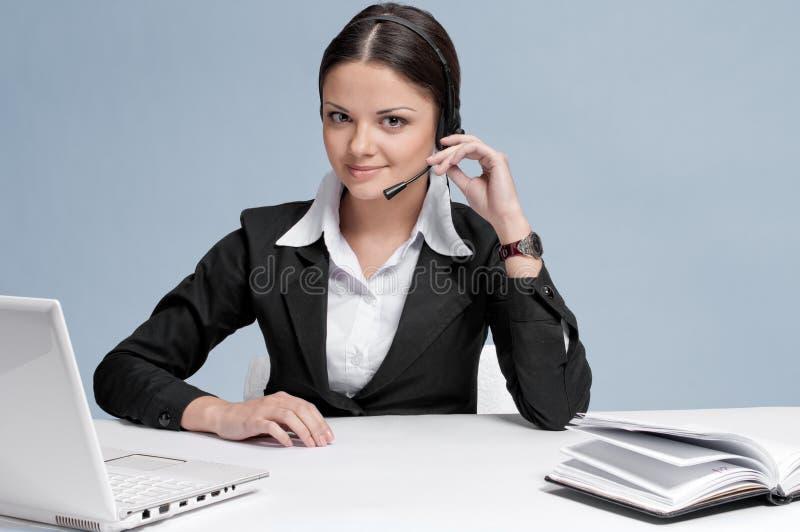 Mulher de negócio com uma comunicação dos auriculares fotografia de stock royalty free
