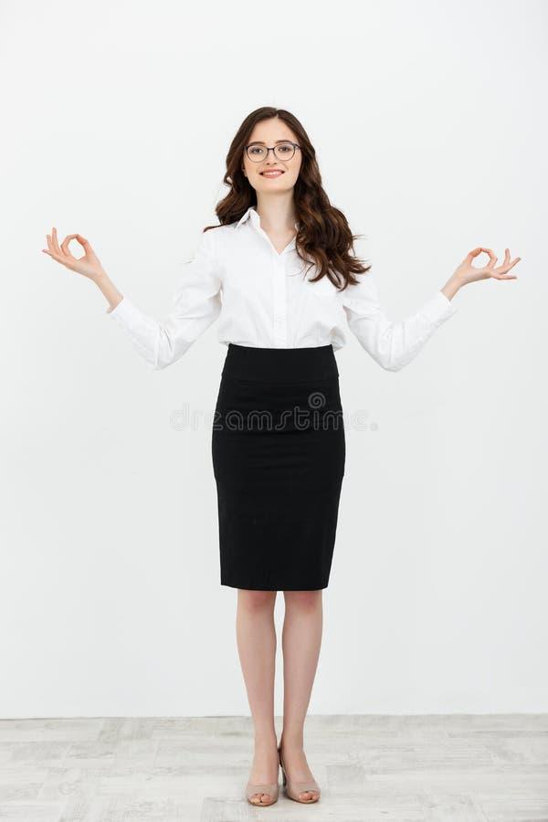 Mulher de negócio completa do retrato do comprimento que faz a ioga de relaxamento do suporte isolada no fundo branco liso imagem de stock royalty free