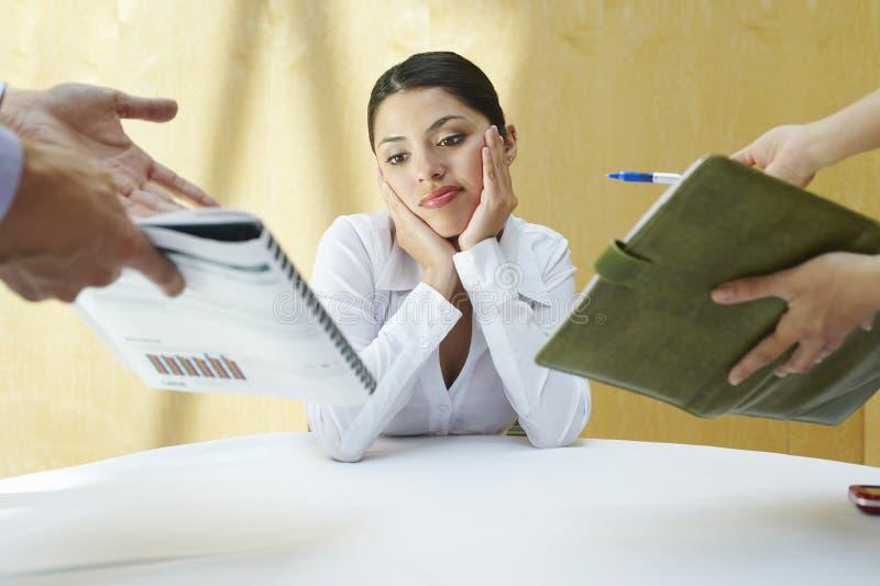Mulher de negócio confusa com colegas imagens de stock