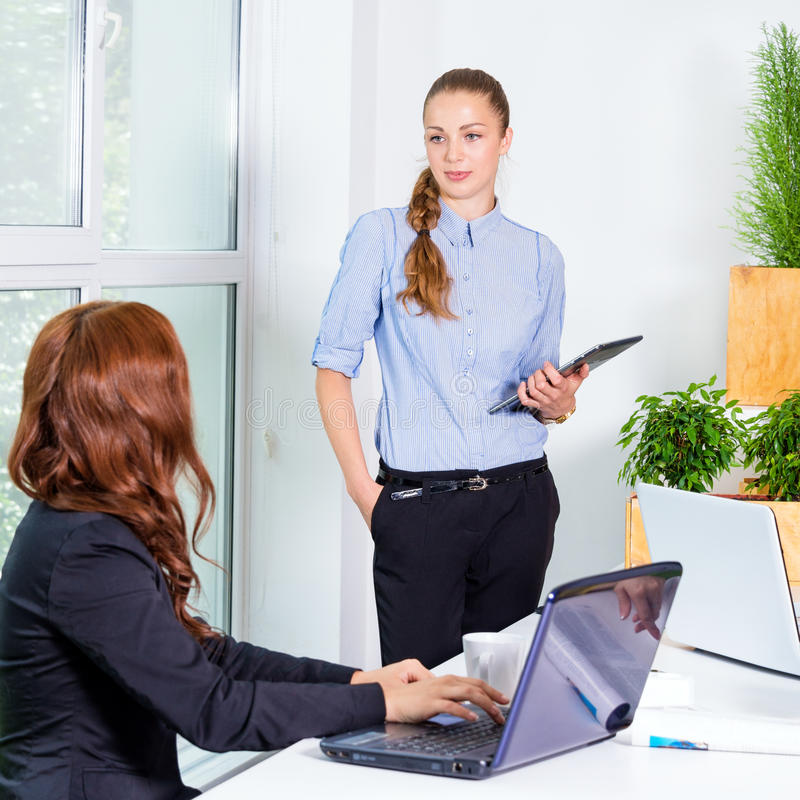 Mulher de negócio consideravelmente nova que dá uma apresentação na conferência ou que encontra o ajuste Conceito dos povos e dos foto de stock