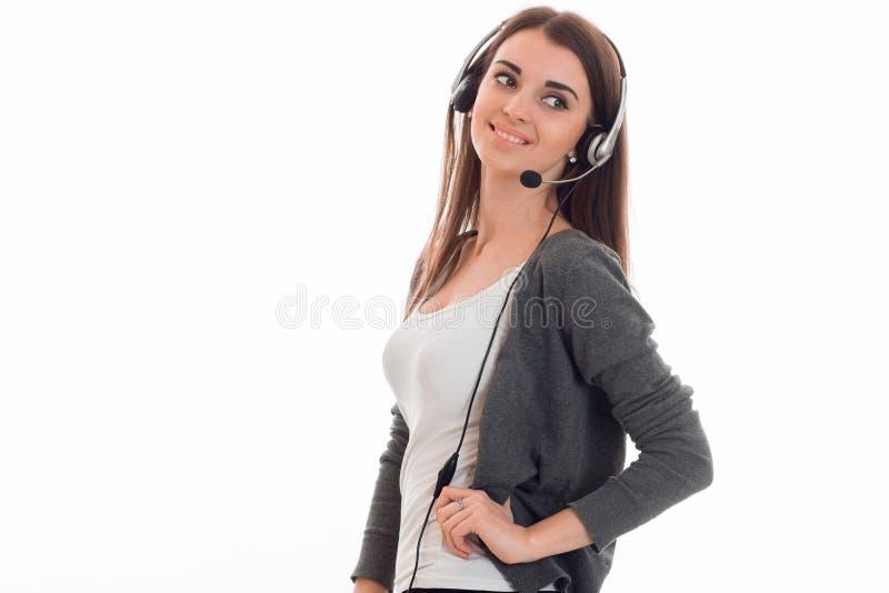Mulher de negócio consideravelmente nova que trabalha no centro de atendimento com os fones de ouvido e o microfone que olham aus fotografia de stock royalty free