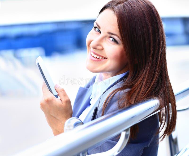 Mulher de negócio consideravelmente nova que usa o telefone celular imagem de stock royalty free