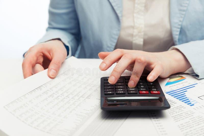 Mulher de negócio da contabilidade financeira que usa a calculadora foto de stock
