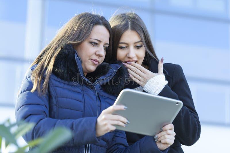 Mulher de negócio de dois jovens com uma tabuleta fotografia de stock