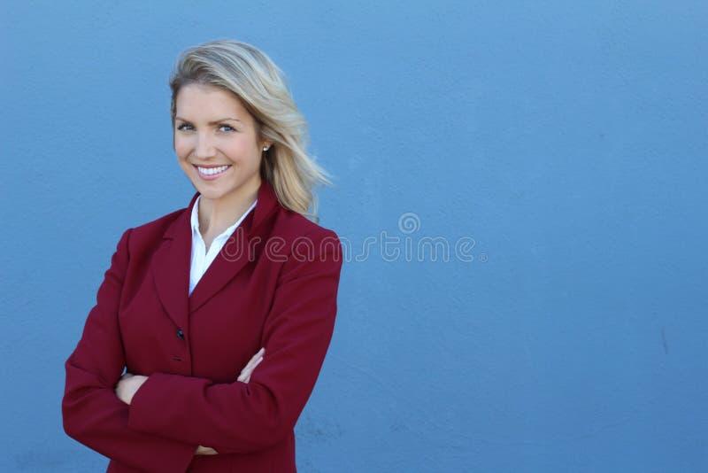 Mulher de negócio de sorriso com mãos dobradas contra o fundo azul Sorriso Toothy, braços cruzados fotos de stock