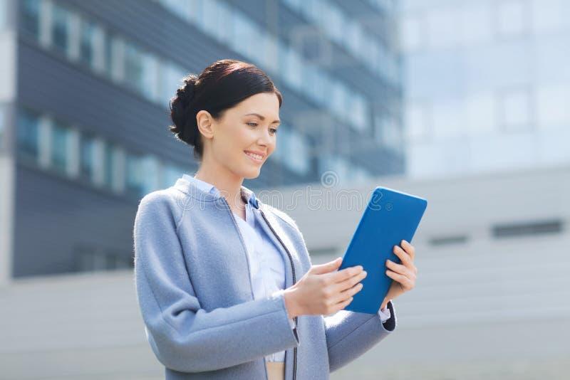 Mulher de negócio de sorriso com o PC da tabuleta na cidade imagens de stock royalty free