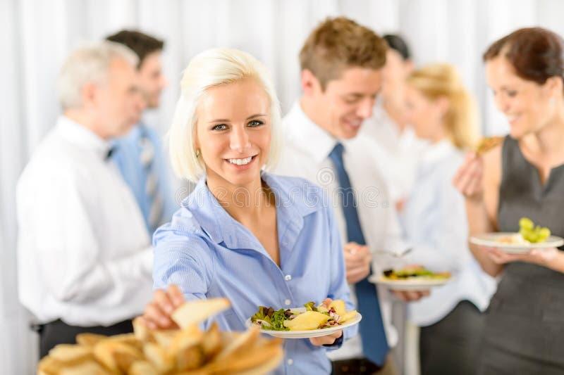 Mulher de negócio de sorriso durante o bufete do almoço da companhia imagens de stock royalty free