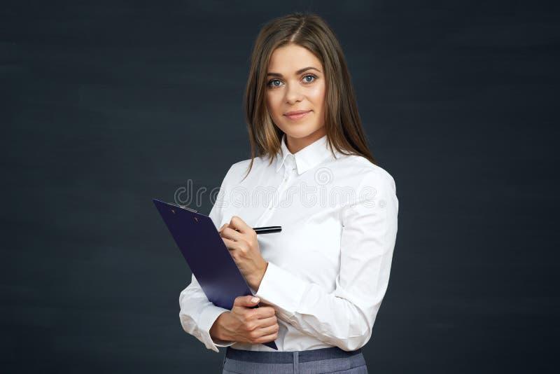 A mulher de negócio de sorriso escreve na prancheta fotografia de stock royalty free