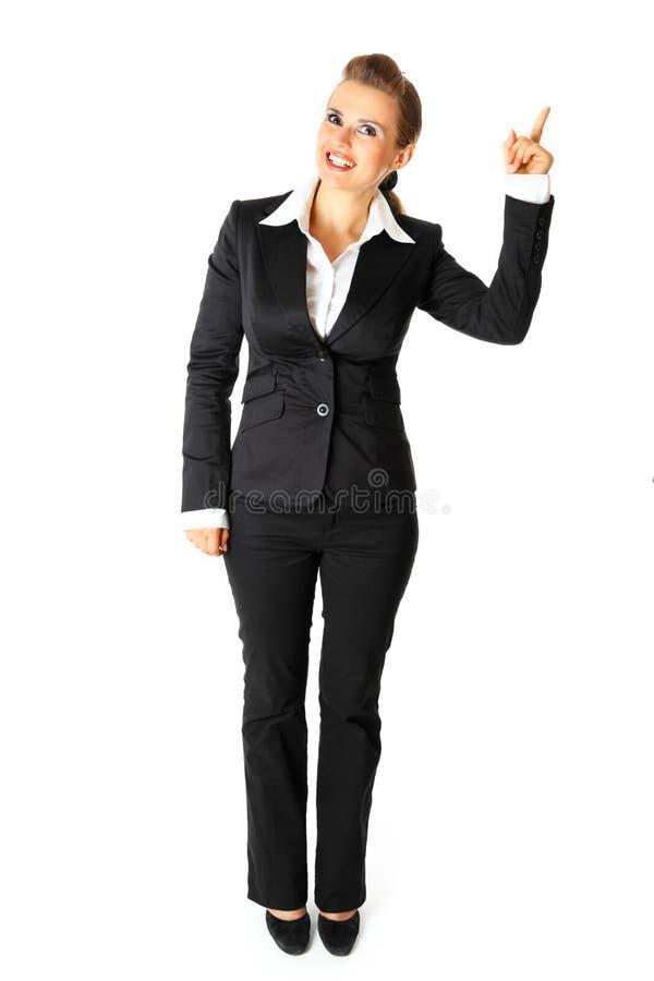 Mulher de negócio de sorriso que aponta o dedo no canto imagens de stock royalty free