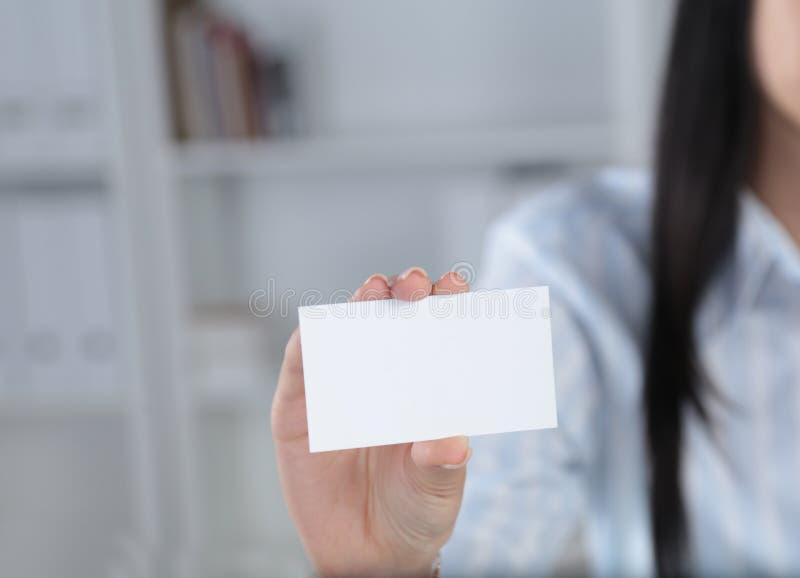 Mulher de negócio de sorriso que entrega um cartão vazio sobre o fundo branco imagens de stock