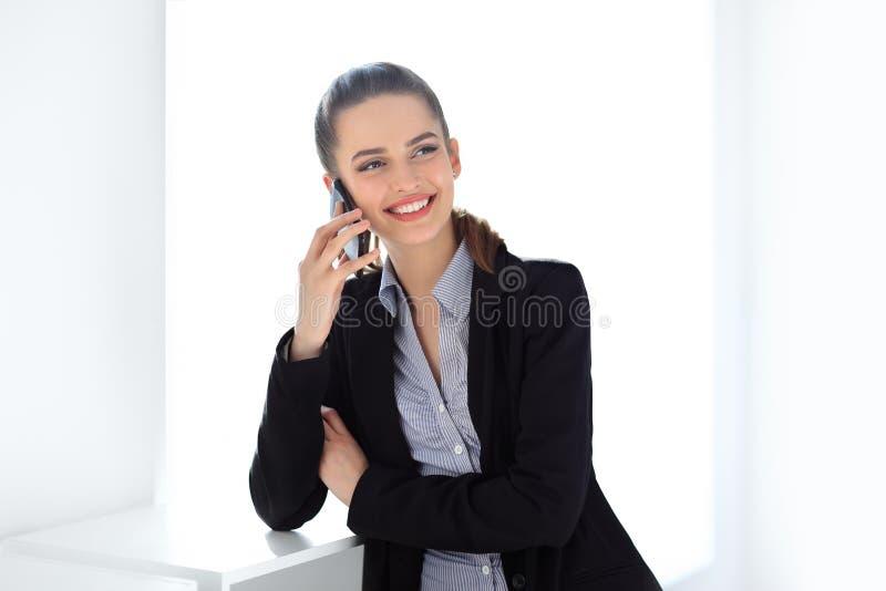 Mulher de negócio de sorriso que fala no telefone celular fotografia de stock royalty free
