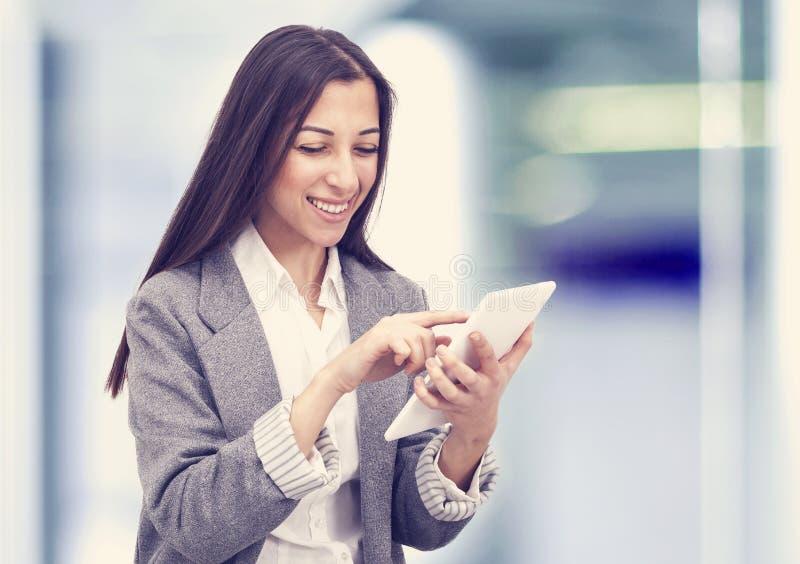 Mulher de negócio de sorriso que guarda um tablet pc no escritório imagem de stock royalty free