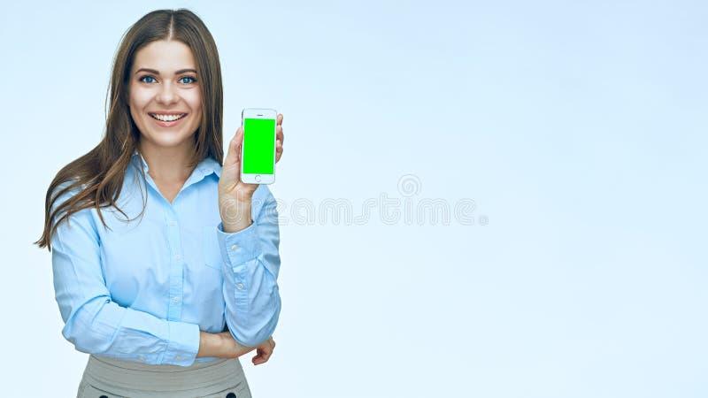 Mulher de negócio de sorriso que mostra a tela do telefone celular foto de stock