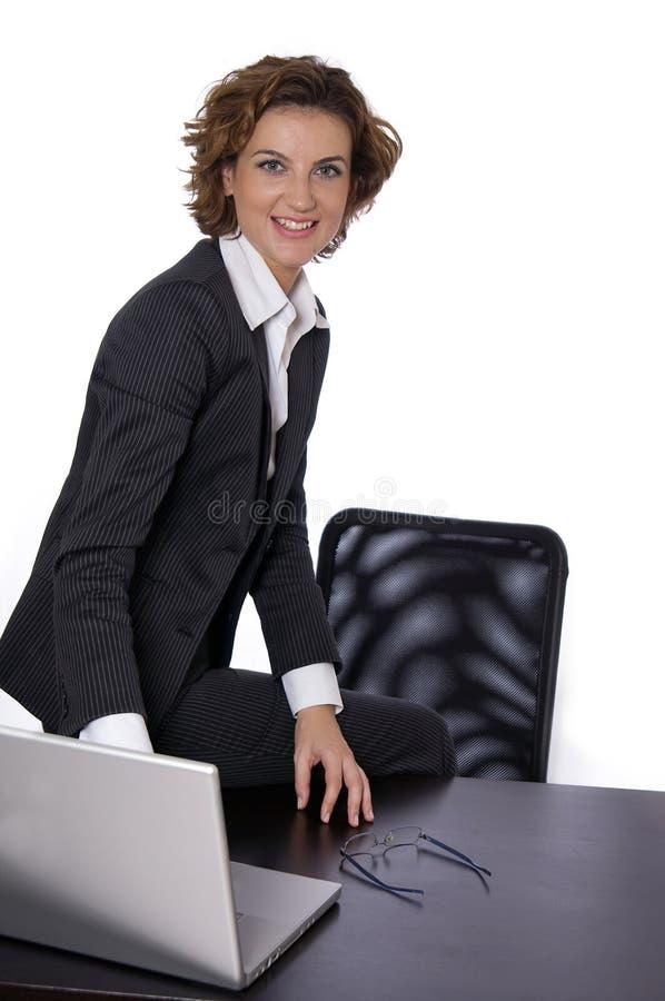 Mulher de negócio de sorriso que senta-se em sua mesa fotos de stock
