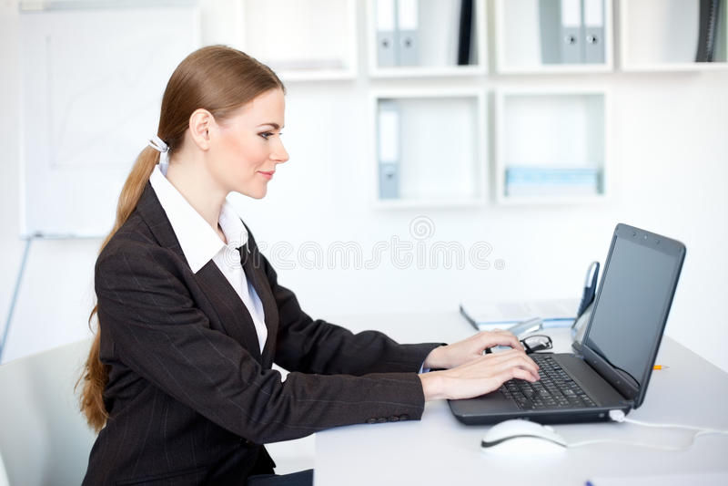 Mulher de negócio de sorriso que trabalha em um portátil no offi imagem de stock