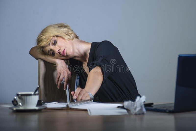 Mulher de negócio deprimida e triste bonita que trabalha na mesa do laptop do escritório que sente cansado olhando desarrumado op foto de stock