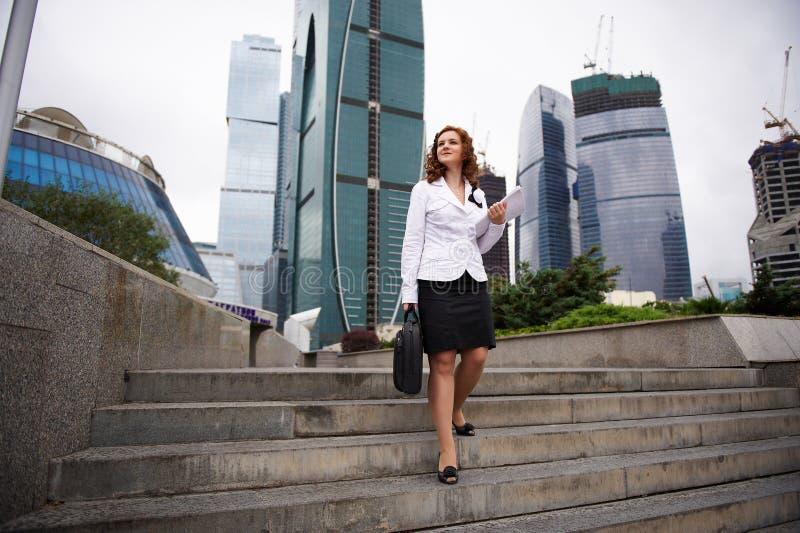 A mulher de negócio desce as escadas à rua fotografia de stock