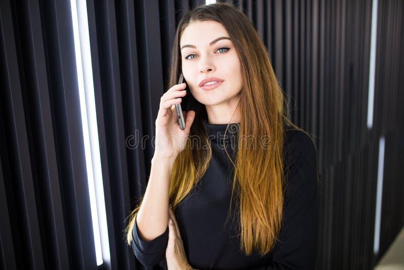 Mulher de negócio do Freelancer que fala no telefone celular com sala do escritório no fundo fotografia de stock